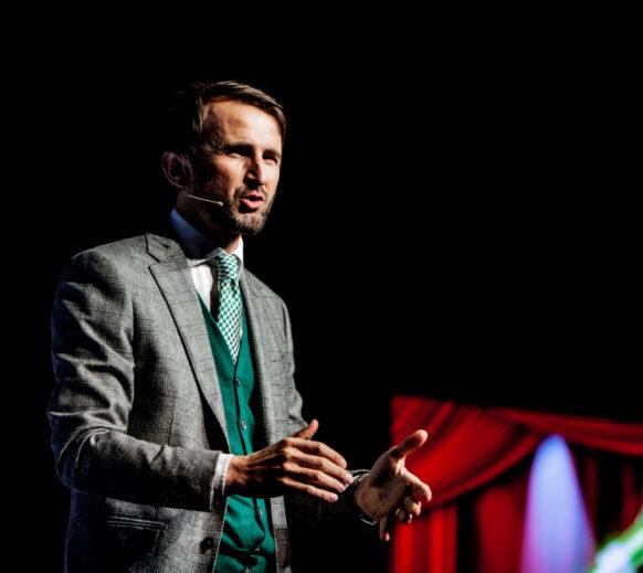 Auf der Bühne steht Gastredner und Mutmacher Jakob Lipp. Er gibt einen Keynote-Vortrag zum Thema Mut im Unternehmen.